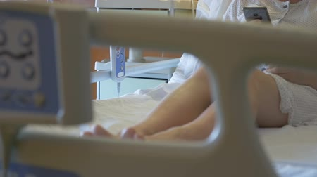 подопечный : Patient in medical cot browses internet. Young woman in the ward holding a smartphone in her hands. Clean and bright room with modern medical equipment. Blurred foreground