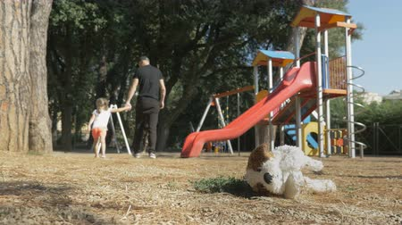 opsporing : A man in black clothes leads a child out of the playground. Childrens soft toy lies on the ground in foreground. Stranger abducted a child Stockvideo