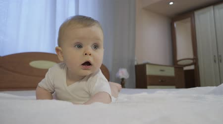 любопытство : Cute baby with blue eyes lying on the bed