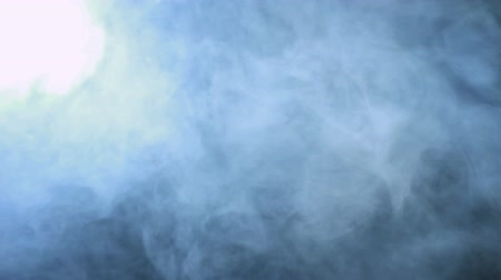hatály : Smoke background. Abstract blue smoke cloud. Smoke in slow motion. White smoke slowly floating through space against black background. Smoke effect. Fog effect. Smoke machine. Studio shot Stock mozgókép