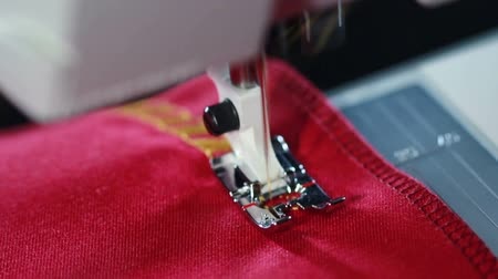 tű : Embroidery machine. Sewing machine embroider pattern on the fabric. Sewing needle stitching seam on fabric in slow motion. Yellow thread pattern on red fabric. Sewing machine slow motion Stock mozgókép