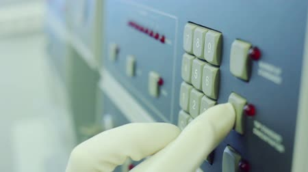 reseach : Scientist in white glove is clicking on hardware buttons of equipment. Dialling code. Closeup. Industrial equipment. Push buttons with numbers. Keyboard on modern laboratory equipment at science lab