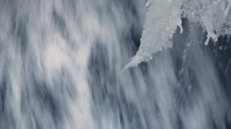 icefall : Flowing water of mountain waterfall in winter. Winter waterfall. Ice waterfall. Fast stream water. Frozen waterfall. Icy waterfall close up. Falling water. Winter cold icy water. Water splashes Stock Footage