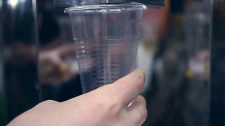 pouring : Water flowing into plastic cup. Water cooler. Closeup of hand holding cup with water. Mineral water pouring in transparent cup and overflow. Natural refreshing water in plastic cup and overflows