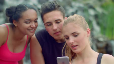 amigos : Three friends using smartphone in park. Young people talking. Cheerful friends smiling. Close up of multicultural people laughing together. Joyful people having fun in park. Friends surfing internet Vídeos