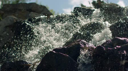 slashing : Water splashes in slow motion. Closeup of waterfall. Splashes of water in sunlight. Water falling over rocks in slow motion. Mountain waterfall. Water splashing on stones. Water rushing over stones