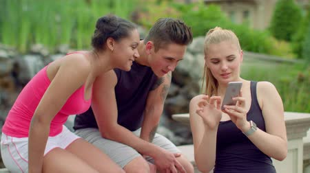 smartfon : Young people watching photos on phone in park. Friends smiling. Happy friends looking photos on smartphone. Multiracial friends having fun together. People phone. Friends using phone Wideo