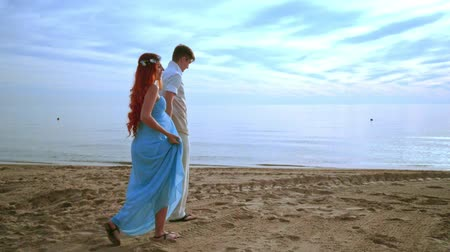 társkereső : Couple walking on beach. Love couple walking beach. Happy couple beach. Beach couple. Pregnant couple holding hands on sea beach. Honeymoon vacation. Blue sky. Romantic dating. Relationship concept