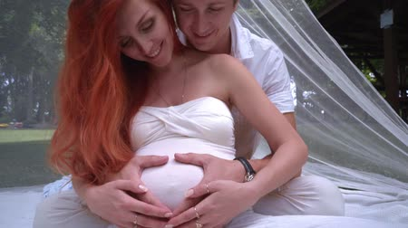 kobieta w ciąży : Happy couple hugging pregnant belly. Couple hands in heart shape on pregnant belly. Pregnant couple holding hands on woman belly. Expecting parent. Pregnancy concept