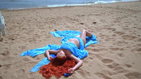 vöröshajú : Red hair woman resting on beach. Close up of pregnant woman lying on sea beach. Young woman relax. Romantic girl relaxing on beach in blue dress Stock mozgókép