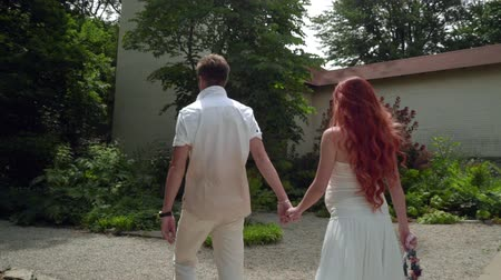 pažba : Rear view of couple walking at backyard of country house. Man and woman walking holding hands backside. Back view of walking couple at park Dostupné videozáznamy