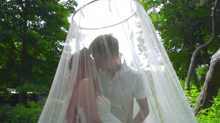 kobieta w ciąży : Love couple kissing. Pregnant couple kissing behind wedding veil at park. Romantic people kissing outdoors. Happy couple. Expecting parents Wideo