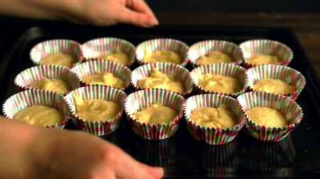panelas : Chef take baking tray with cupcakes. Cooking cupcake. Cup cake dough in paper forms. Raw cake on baking tray. Man hands pick up baking tray with raw dessert Stock Footage