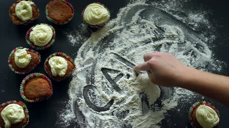 slova : Inscription cakes on white flour spills at kitchen table. Baking cupcakes concept. Home baking. Finger writing word cakes on white flour background. Baking cakes concept. Cupcakes on table