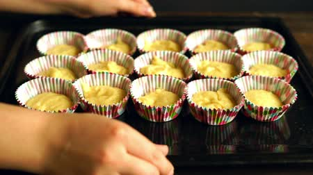 bandeja : Cooking cupcake. Chef making muffins. Baking muffins. Raw dough cake in cupcake tray. Hands put cupcake tray on wooden table. Cup cake preparation. Vanilla muffins on baking pan. Homemade cakes