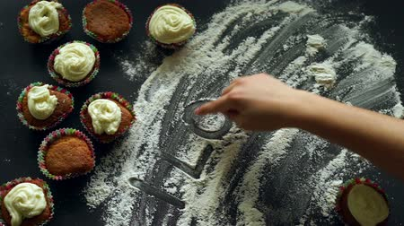 miłość : Sweet love concept. Inscription I love you on white flour. Romantic background with cupcakes cakes. Cooking dessert for valentines day. Sweet delicious. Finger writing words I love you on flour Wideo