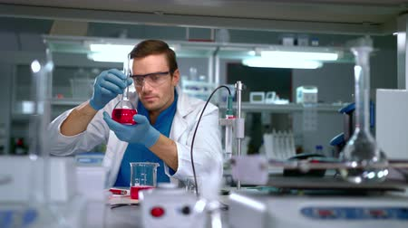 lekarstwo : Chemist studying liquid in glass flask at modern lab. Laboratory worker finding a cure. Scientist working at research laboratory. Doctor doing medical research at science lab. Chemistry lab