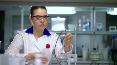 kimyasallar : Female scientist working with equipment in research laboratory. Researcher preparing laboratory equipment. Lab worker working with lab equipment. Young assistant preparing laboratory equipment in lab Stok Video