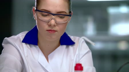 фармацевт : Lab woman working in lab. Scientist woman writing down research results. Female scientist working in lab. Student working in research laboratory. Young scientist writing scientific report in lab Стоковые видеозаписи