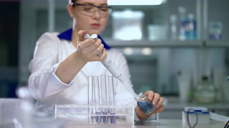 enstrüman : Researcher working in chemical lab. Female scientist doing experiment in research laboratory. Scientist woman working with chemical liquids in laboratory. Lab worker pouring liquid in test tubes Stok Video