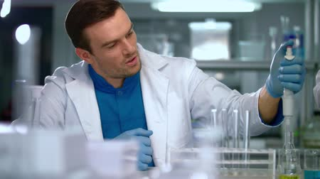 farmacologia : Scientist man using pipette in lab. Researcher with dropper working in laboratory. Scientist student working in lab. Lab worker using laboratory equipment. Laboratory scientist working with pipette