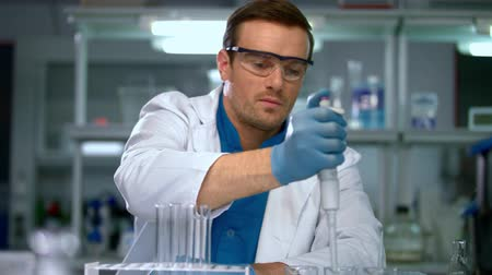 prova : Male scientist conducting research in chemical lab. Scientist working with chemical liquid in research laboratory. Scientist filling test tubes with samples in laboratory. Scientist working in lab