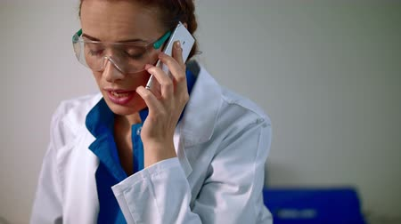 мобильный телефон : Woman scientist talking on phone. Medical communication. Portrait of female scientist speaking on the phone. Scientist woman talking on phone. Young scientist in lab coat talking phone