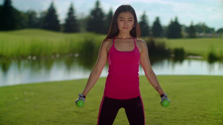 súlyzó : Asian woman lifting weights outdoor. Attractive woman working with dumbbells. Fitness woman exercising with small weights in park at summer. Sport woman weight lifting exercise. Athletic girl workout