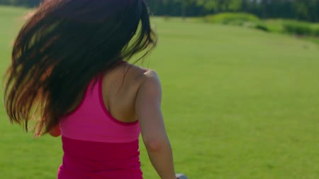 tüyler : Long hair woman running in park. Back of running woman in slow motion. Close up of woman running away outdoors. Running woman with long hair. Fit girl run outdoors. Sport girl run at morning