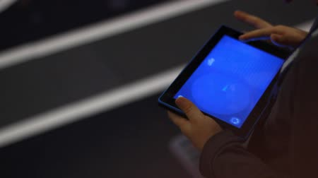 zobrazit : Kid hands playing video game on tablet pc. Closeup of hand kids playing video game on tablet. Video gaming on tablet computer. Child hand touch screen tablet