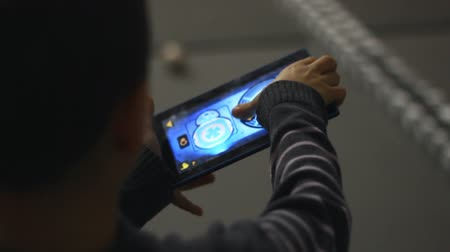 技术 : Boy gaming with tablet computer. Boy playing with tablet computer. Touch screen video game controller. Touch screen controlling joystick. Kid hand controlled game with tablet pc 影像素材