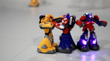 pojedynek : Robots fighting show. Closeup of remote control toy robots fighting. Close up of fighting robots on white floor. Transformer robot boxing. Toy robots fight. Battle robotic toy