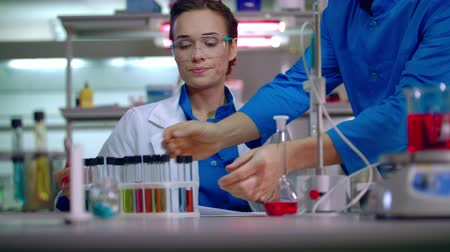 auxiliar : Woman chemist writing research data in lab. Lab worker pick up test tube rack. Chemist writing chemical research report. Female chemist working in chemical laboratory