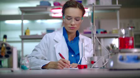 przychodnia : Lab doctor writing clinical data research. Clinical research in medical lab. Woman lab writing medical research report. Medical researcher writing research results Wideo