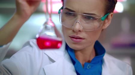 pharmaceuticals : Medical researcher in medical lab. Close up of female lab researcher doing medical research. Woman scientist. Pharmaceutical research. Medical scientist doing laboratory research. Liquid in lab flask