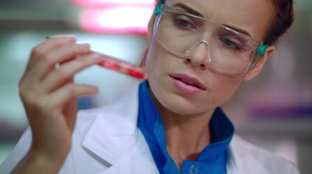 clínico : Female doctor analyzing liquid in test tube. Closeup of lab doctor doing medical research. Medical researcher doing clinical trials. Woman scientist doing medical research. Woman doctor face