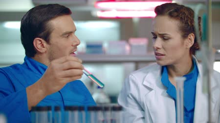 teste : Scientist team working in lab. Scientist discussing liquid sample in test tube. Group of scientists in lab. Male and female scientist talking about science research result Stock Footage