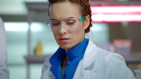 clínico : Lab researcher in laboratory. Close up of female scientist in safety glasses. Medical researcher sitting in clinical lab. Portrait of lab woman working in research lab. Woman scientist face Stock Footage