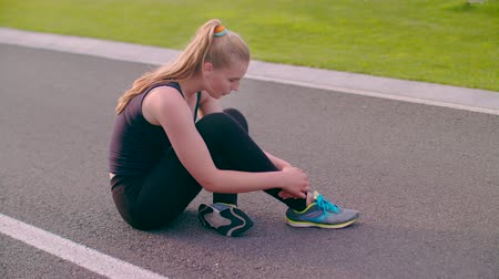 asfalt : Exhausted woman sitting on asphalt road after running marathon. Tired woman runner breathing after running hard. Fitness woman after running exercise sitting on road. Tired runner. Exhausted runner