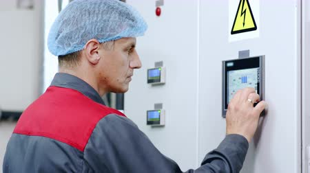 érintés : Factory worker working with touch screen display of industrial computer equipment. Technical employee programs control screen monitor. Technical engineer control industrial screen touch panel