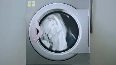 indústria : Industrial washing machine washing clothes. Laundry machine working. Industrial machine washing clothing. Laundry washing machine. Industry laundry service Stock Footage