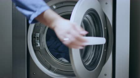 cleaner : Loading washing machine. Load clothes to washer machine. Female hand put uniform in laundry machine. Load clothes laundry washing machine. Preparing laundry washing Stock Footage