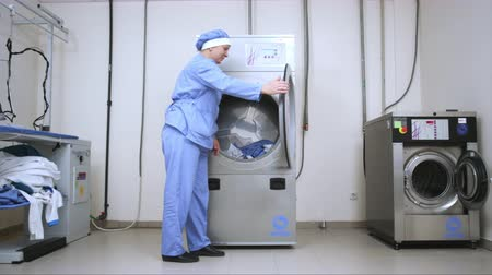 kurutma : Female worker loading washing machine at hotel laundry. Woman working at industrial laundry service. Employee loading laundry in industrial washer. Commercial laundry room. Stok Video