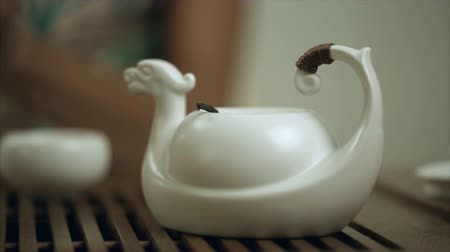 tradição : Female hand brew tea in teapot cup. Close up of brewing tea in teapot. Traditional process of tea drinking preparation. Traditional green tea brewing process