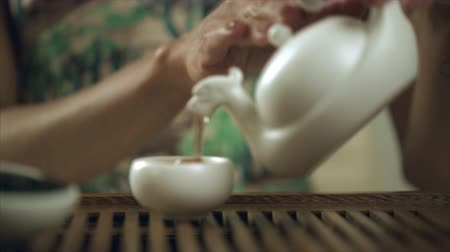 tradição : Woman hand pour tea from teapot to teacup. Pouring tea drinking in porcelain bowl. Close up female hand pouring cup tea drink. Traditional tea pouring in teacup Stock Footage