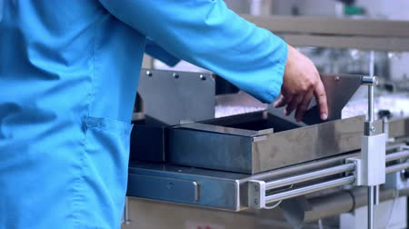 пробирка : Pharmaceutical manufacturing process. Close up of worker hands working with pharmaceutical packaging machine. Manufacturing pharmaceutical vials on production line. Medical ampoules packaging process