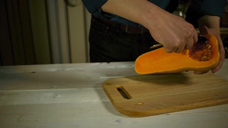 gastronomia : Chef removing pumpkin seeds. Cleaning out pumpkin slice. Preparation food. Pumpkin carving. Male hands preparing pumpkin for cooking on wooden board in kitchen. Healthy food ingredient