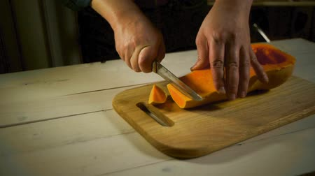 gastronomia : Cutting raw pumpkin slice. Preparation for cooking. Male hands preparing pumpkin for cooking on wooden. Man cutting orange pumpkin piece. Healthy food ingredient. Raw pumpkin cut Vídeos