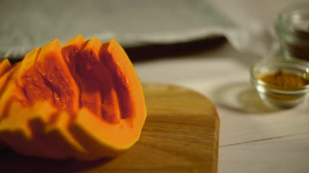 deski : Raw pumpkin pieces. Close up pumpkin slices on wooden board. Pumpkin slices with spices and herbs. Seasoning food on kitchen table. Vegetarian food. Cut pumpkin spice. Sliced vegetables