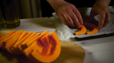bandeja : Chef put cut pumpkin on baking tray. Raw pumpkin pieces baking cookies. Close up of male hands putting pumpkin slice for baked. Seasonal vegetable cooking. Pumpkin dish preparing Stock Footage